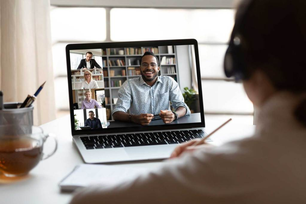 Back view of female employee have webcam conference on computer with multiracial colleagues, woman talk brainstorm on video call with diverse coworkers, engaged in web team online briefing from home