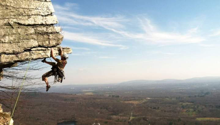 climber hanging from cliff with horizon in background