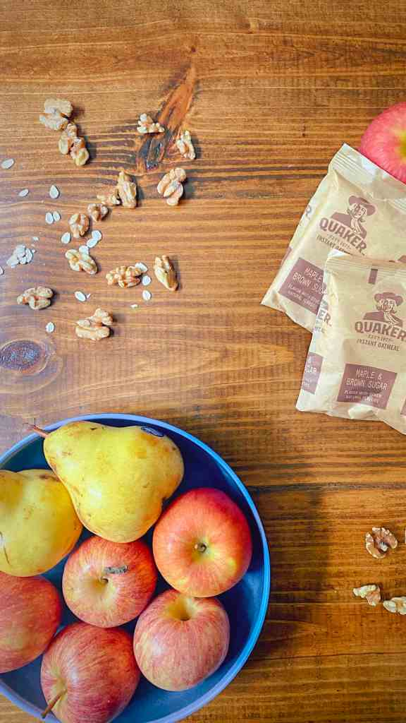 Apples and pears in a bowl with oatmeal packets and walnuts.
