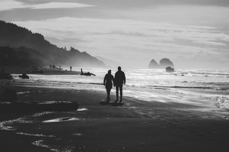black-and-white-image-of-couple-walking-on-beach