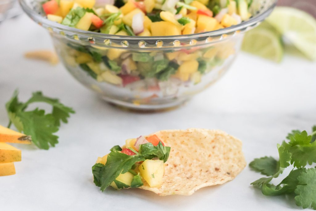 raw mango salsa in bowl with chip dipped in it