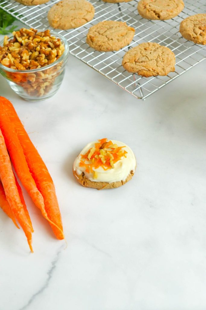 carrot cake mix cookies on cooling rack with walnuts in bowl and fresh carrots on the side