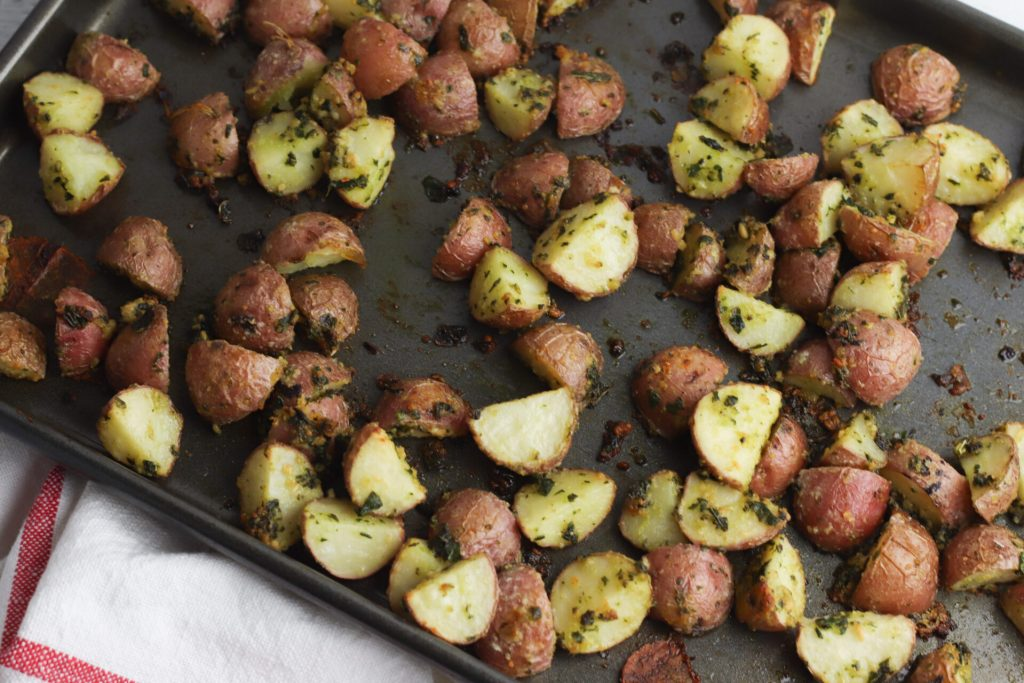 Take a break from your usual potato recipes to try out these delicious Pesto Roasted Potatoes! The fresh flavor of the pesto mixed with the smooth potatoes is the perfect combination. Plus it only takes 5 minutes to prepare before you roast!