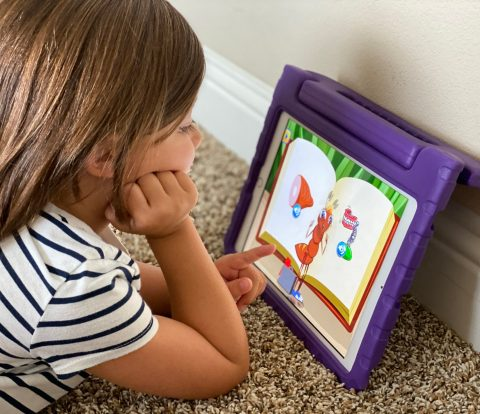 girl playing iPad on purple iPad