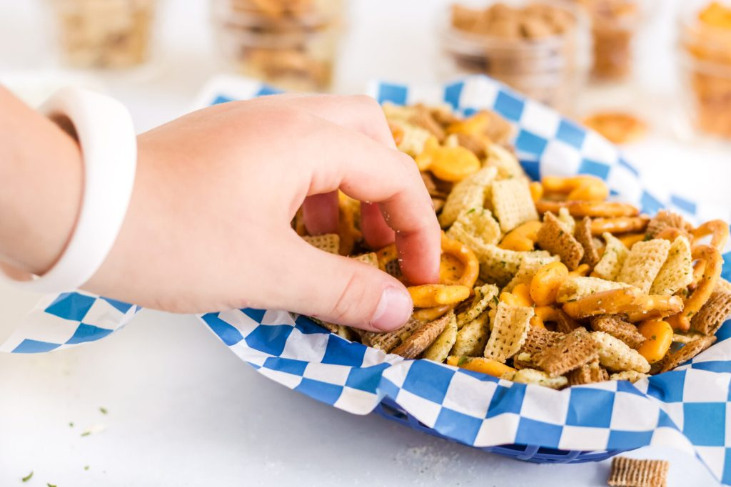close up of hand grabbing air fryer Chex mix