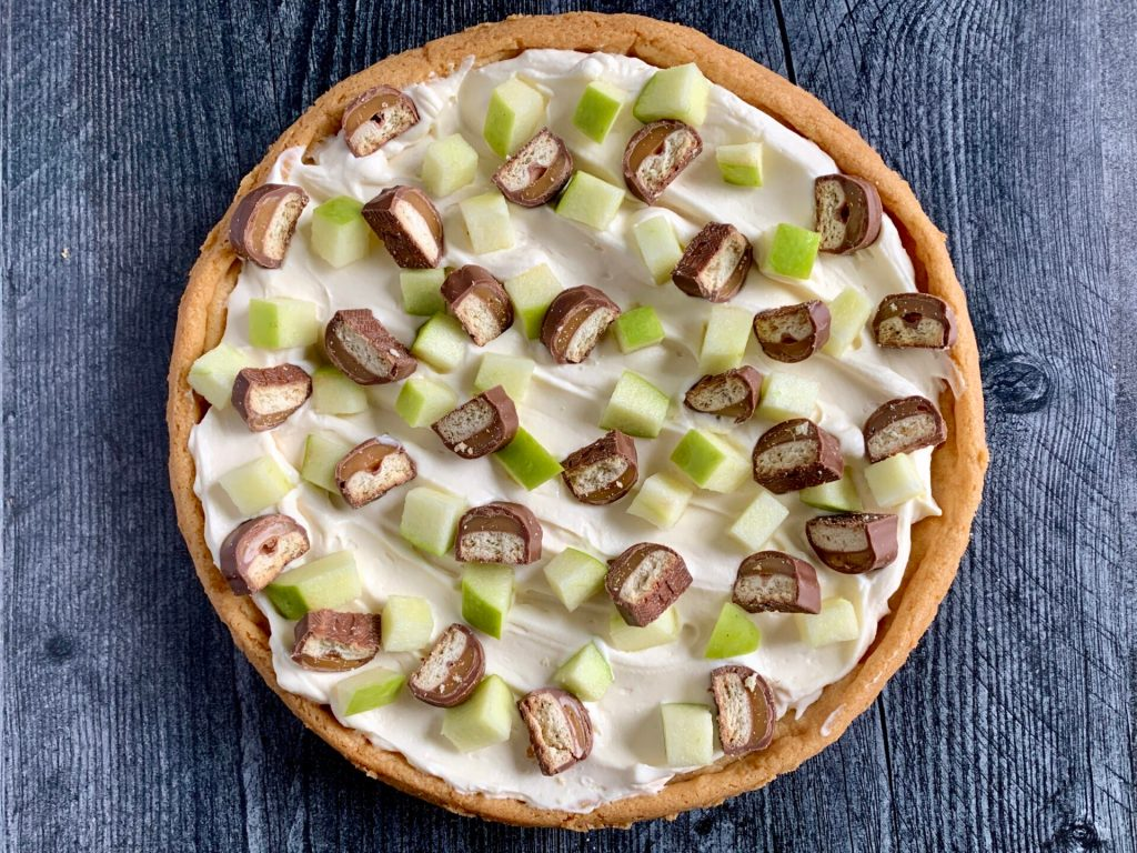 apple dessert pizza with sauce, apple, and Twix