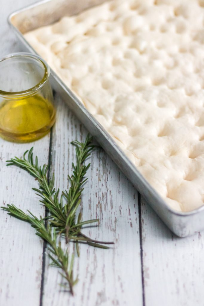risen rosemary focaccia bread with rosemary sprigs on the side