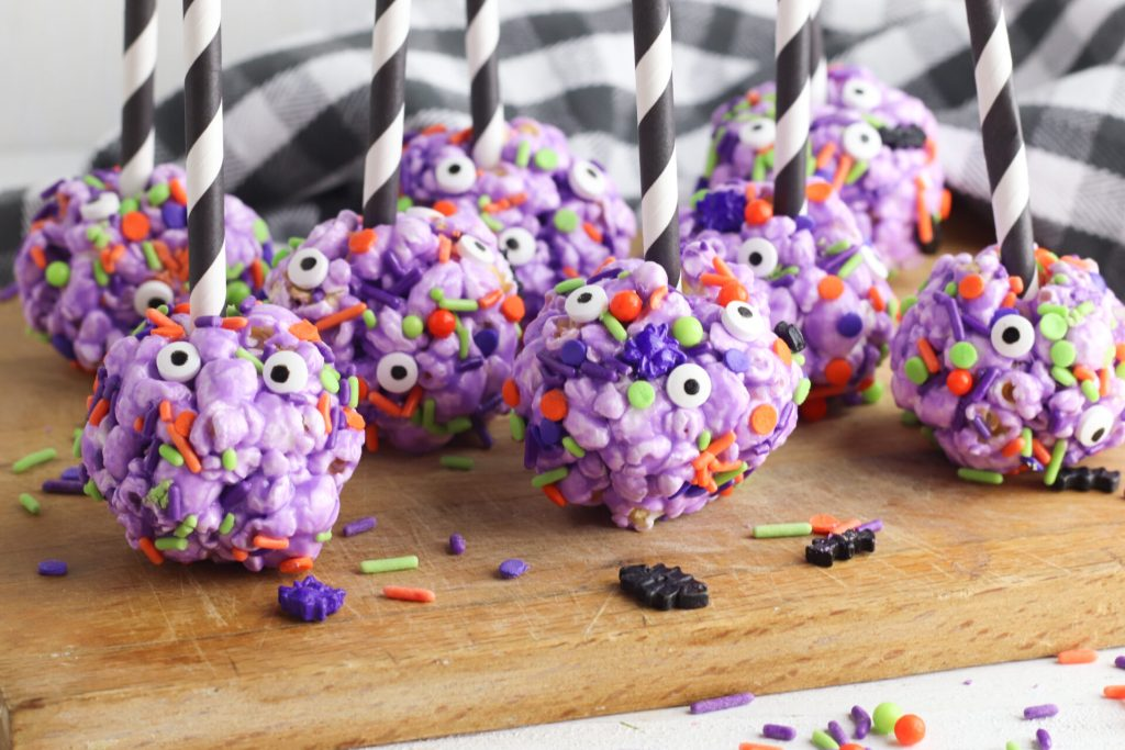 halloween popcorn balls on a wooden cutting boards with halloween sprinkles