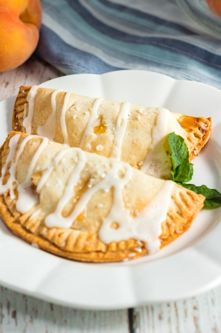 Two peach pies on white platter