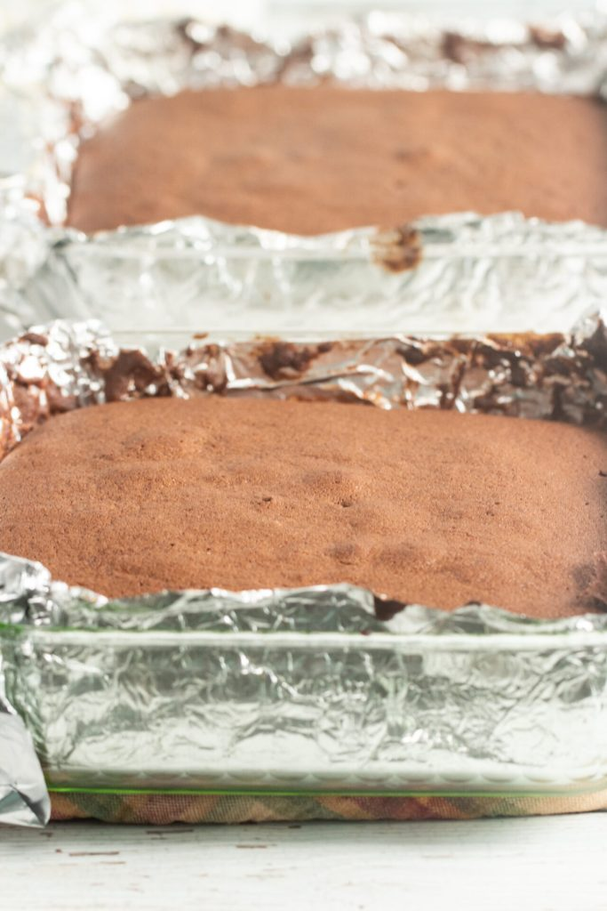cake fresh out of the oven in glass pans with foil