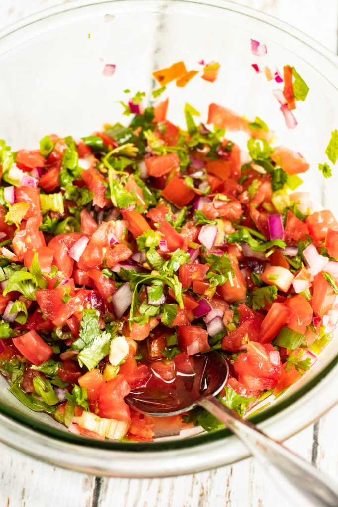 pico de gallo in a glass bowl with serving spoon