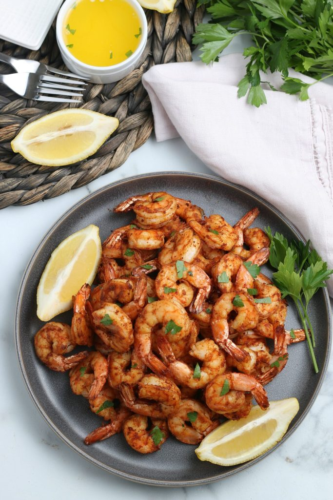 air fryer shrimp on a gray plate with lemon slices