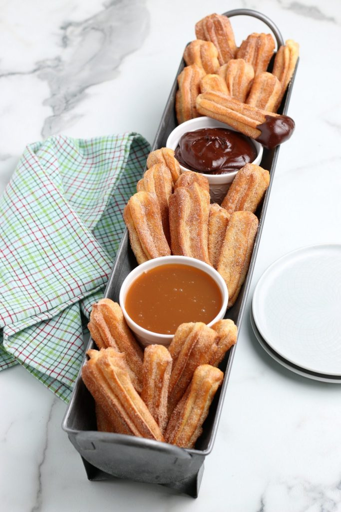 air fryer churros dipped in cinnamon sugar with caramel and chocolate sauces