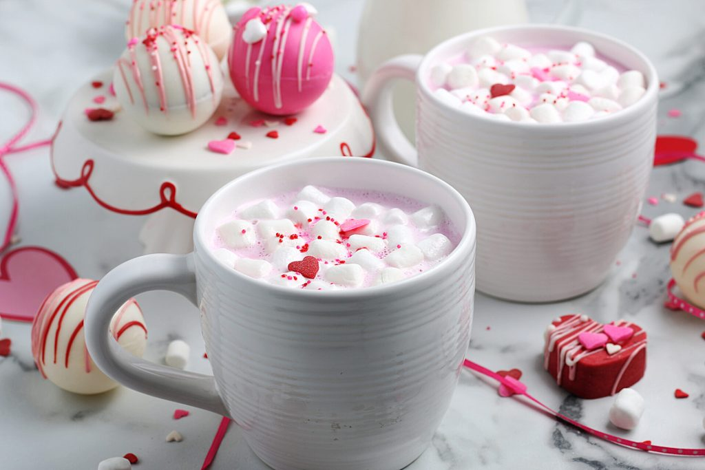 pink hot chocolate with marshmallows in white mugs surrounded by hot chocolate bombs