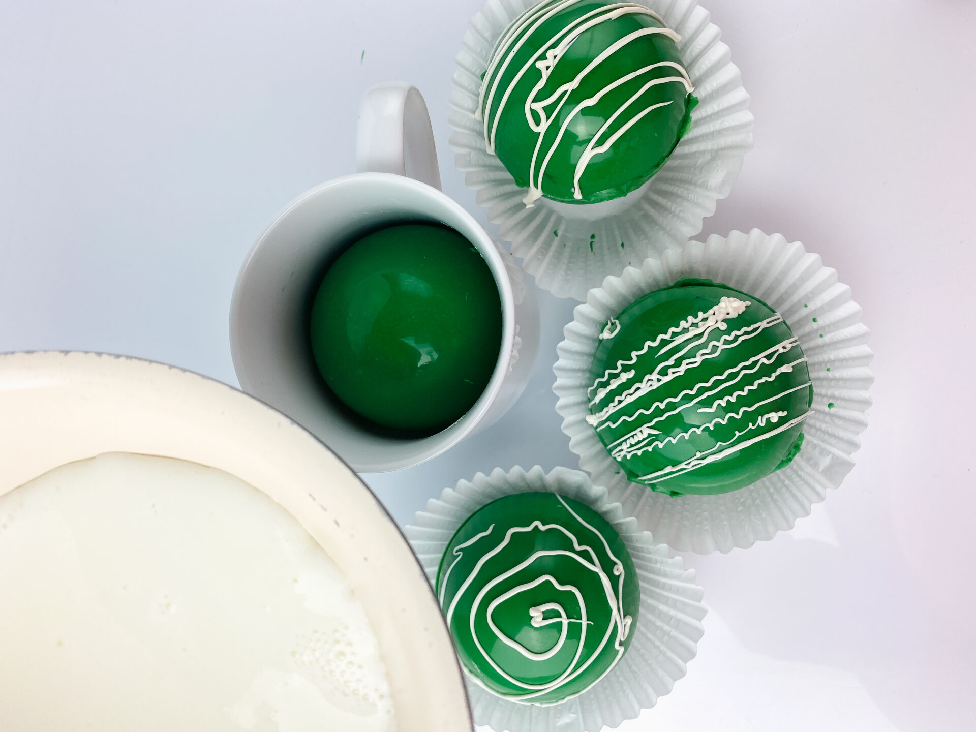 pouring milk on top of green hot chocolate bombs