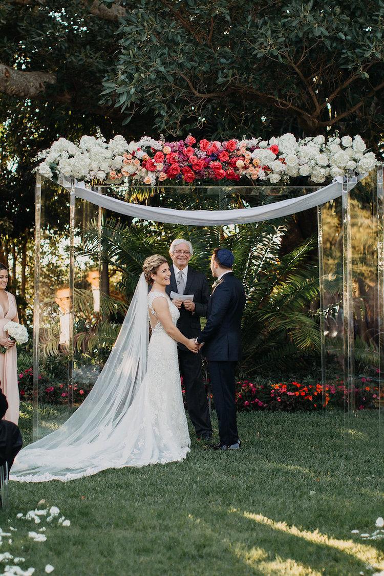 Elegant garden wedding venue with lucite ceremony arch