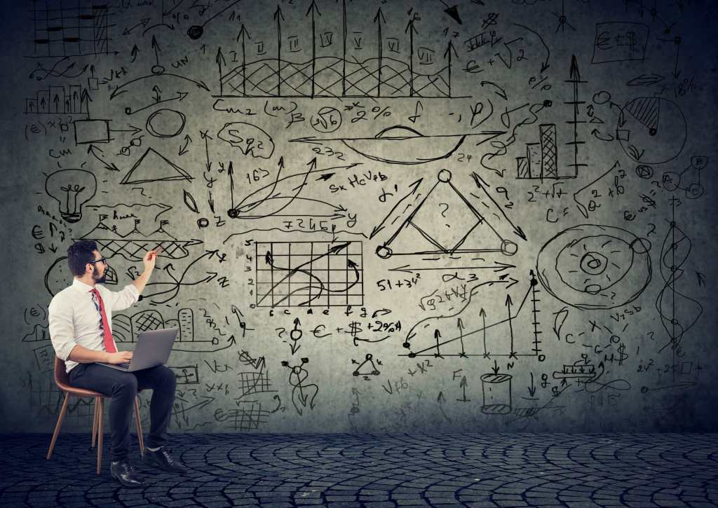 Man in suit sitting on a chair looking at a wall of plans for his project displayed in a sketched doodle fashion - he is pointing at the plans while his laptop is on his lap