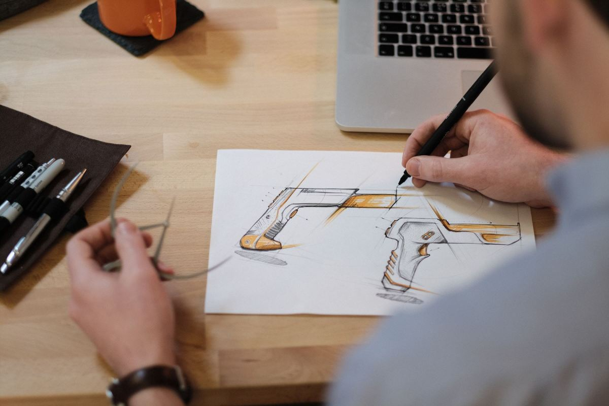Designer working on ideation design sketch at desk with macbook and tools to hand