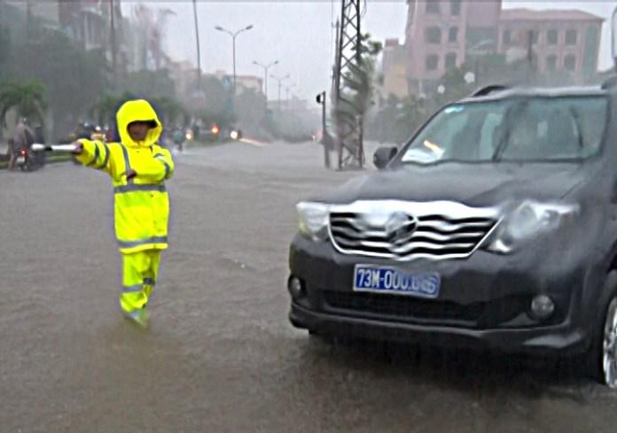 CSGT hướng dẫn phương tiện đi qua các tuyến đường ngập lụt đảm bảo an toàn