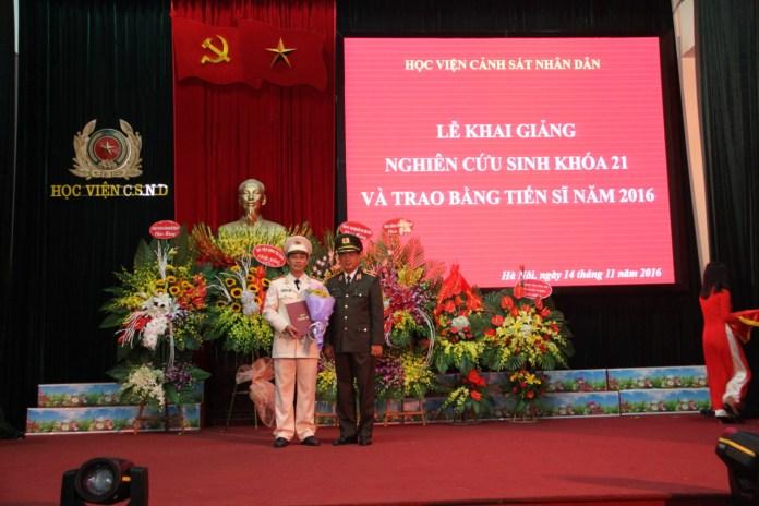Đồng chí Thiếu tướng, PGS.TS Đỗ Ngọc Cẩn, Phó Tổng cục trưởng Tổng cục Chính trị CAND trao bằng tiến sĩ cho đồng chí Trung tá Hoàng Giang Nam.