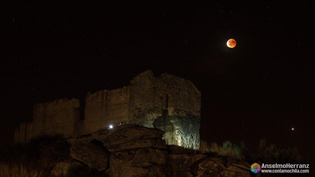 Ermita de San Isidro iluminada por linternas y frontales, al fondo el eclipse total de luna.