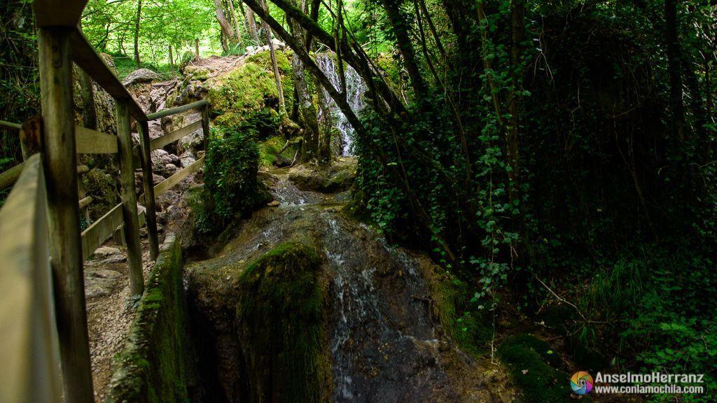 El agua vierte por las paredes hacia el río Urederra.