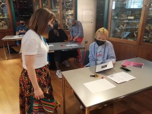 A seated woman shows her completed woven marker to another women standing to her right hand side. Both women wear face masks. In the background are more participants and the Grant Museum display cases.