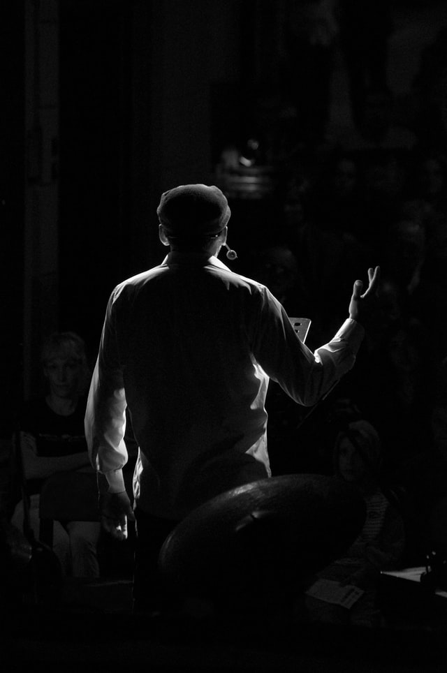 Man singing on a stage, pictured from behind.