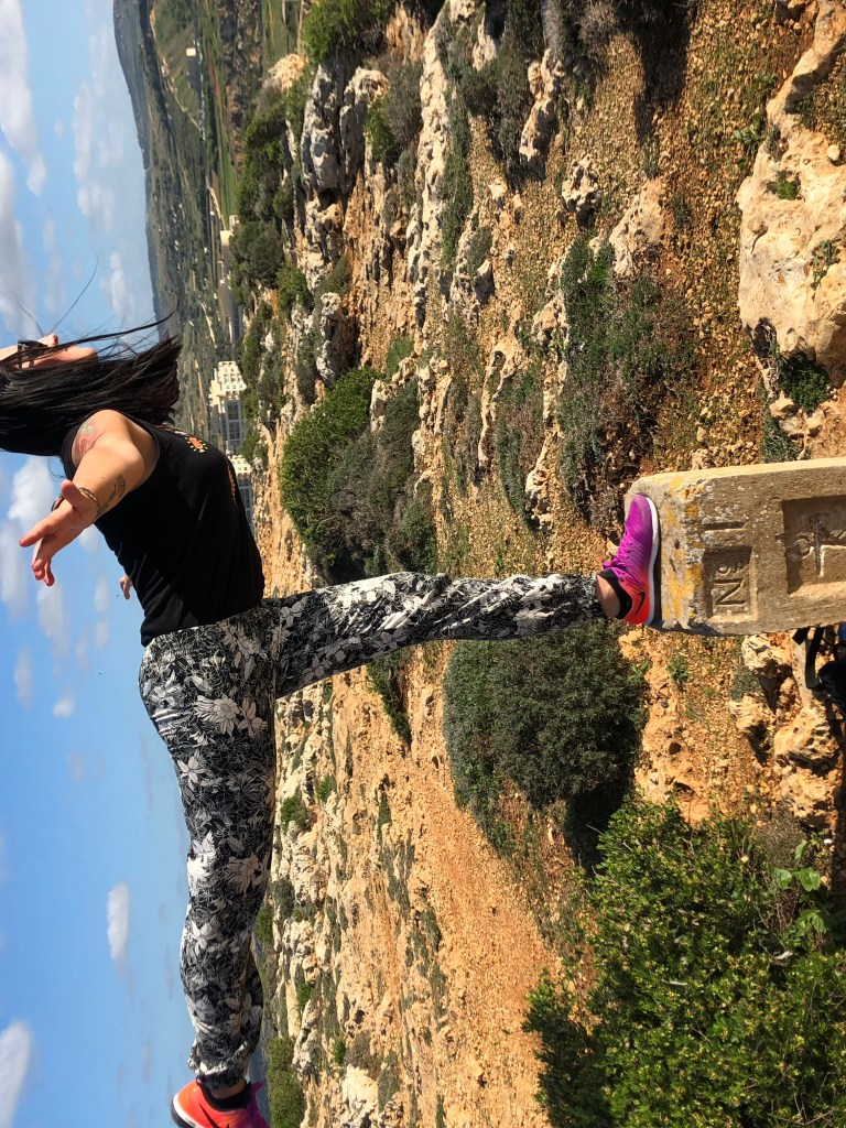 Timi Orosz in Malta on a hike balancing on a stone in nature