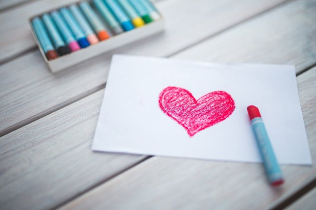 Heart drawn in pink crayon on a piece of paper