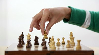 stock-footage-people-s-hand-moving-chess-pieces-isolated-over-a-white-background