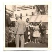"""Barco danés """"Alabama"""" Pepe Santana con una familia danesa y de espaldas """"Bruno"""", vendiendo manteles y muñecas. 1955."""