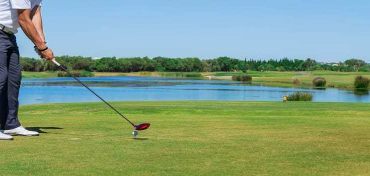 Golf enthusiast teeing off over a water hazard