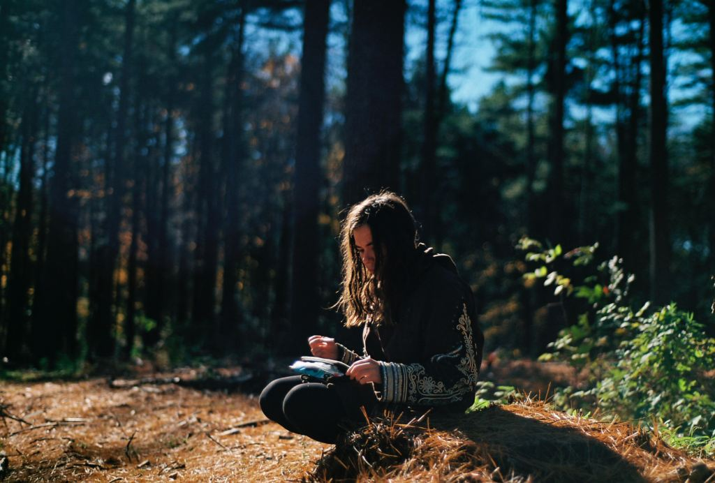 Rest during Late Winter seasonal junction | woman sitting on a log in the forest journaling