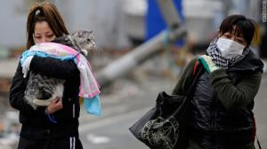 Two women walk in a tsunami devastated street in Hishonomaki, Miyagi Prefecture, on March 15, 2011