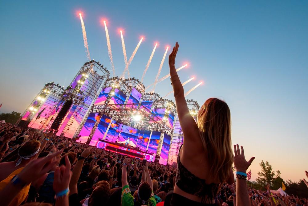 crowd shot girl raises hand edm festival fireworks