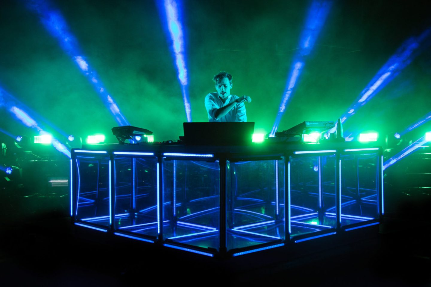 flume DJ on stage, blue setup with green lights, hand in the air