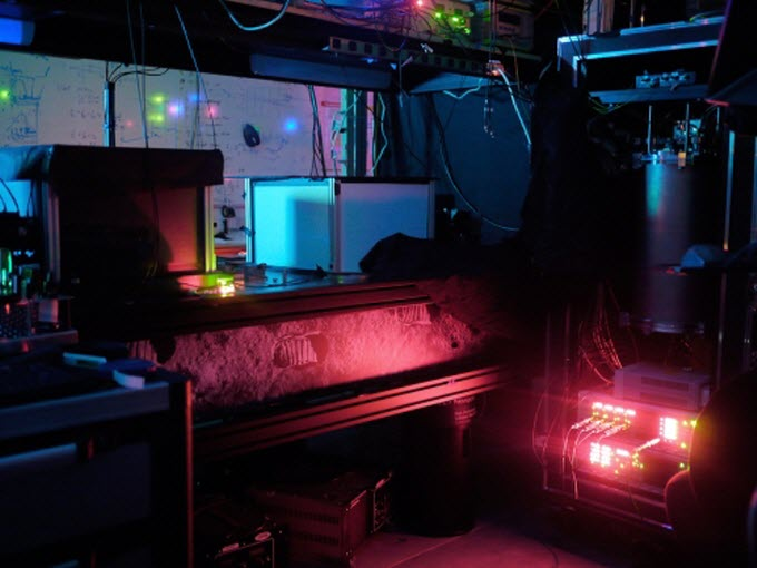 University of Waterloo laboratory where scientists entangled three photons. NIST's single-photon detectors were chilled to near absolute zero in the refrigerator (large blue cylinder). The experiment had to be performed in the dark because of the need to detect very low light levels. Credit: Shalm/NIST