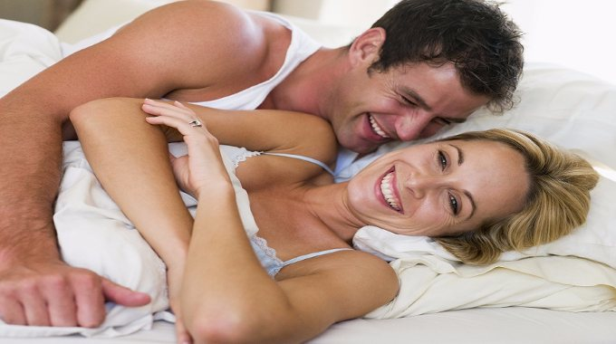 Couple in bed laughing-compressed