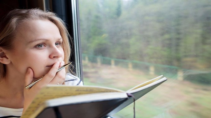 Woman taking notes on a train-compressed