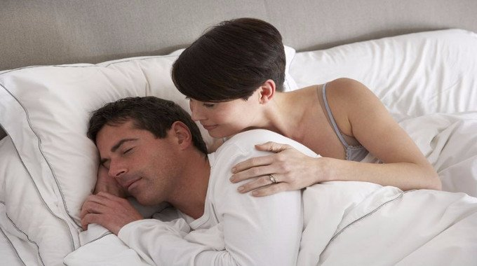 Wife waking her husband in bed-compressed