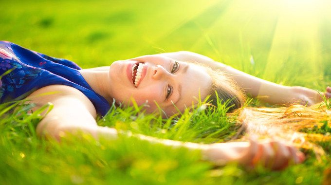 happy woman lying in fields-compressed