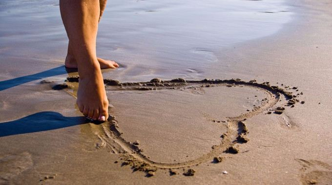 woman drawing a heart in the sand at the beach-compressed