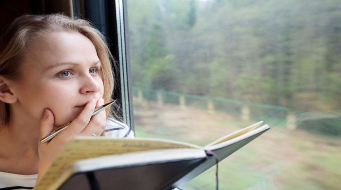 Young woman on a train writing notes-compressed
