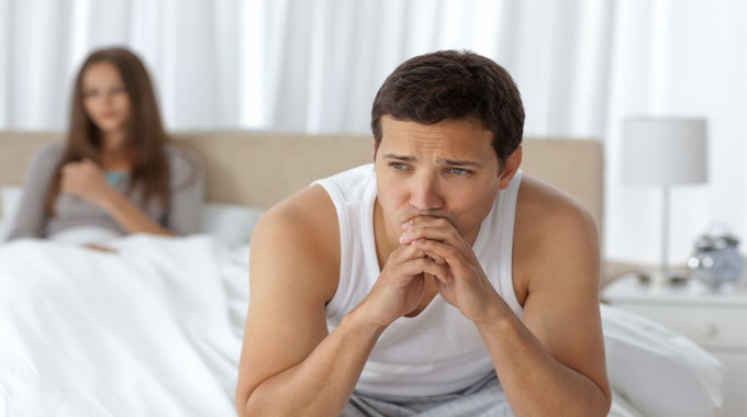 pensive-man-having-a-headache-sitting-on-the-bed