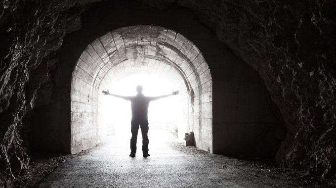 man-stands-in-dark-tunnel-with-glowing-light-compressed