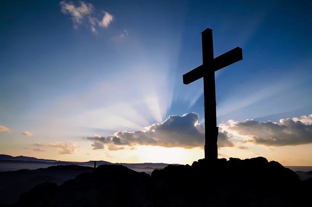 Imagem ilustrativa de uma cruz vazia  com um fundo azul e luzes saindo das nuvens.