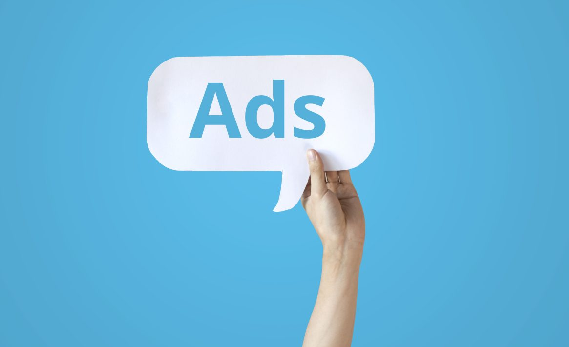 Human hands holding a bubble speech of word 'Ads' in all blue background