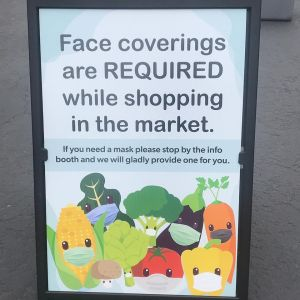 Signage at market noting that face coverings are required.