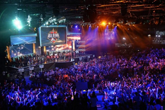 """Visitors cheer for international teams during the tournament of the computer game """"League of Legends"""" on May 8, 2014 in Paris. Launched late in 2009 by American video game publisher Riot Games, """"League of Legends"""" is a game in which teams of five players compete in a virtual arena, killing each other using different powers and equipments in the goal to capture the enemy base. According to Riot Games, more than 67 million people play each month, with peaks of more than 7.5 million concurrent players at peak hours. The game will last four days starting today. AFP PHOTO / LIONEL BONAVENTURE        (Photo credit should read LIONEL BONAVENTURE/AFP/Getty Images)"""